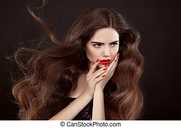 Beauty hair. Red manicure. Brunette girl with long shiny...