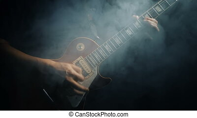 Man's hands playing electric guitar, - Closeup of man's...