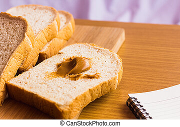 peanut butter and breakfast on wood table with book
