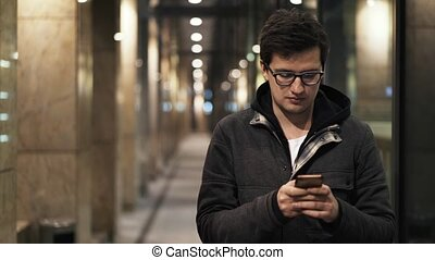 Young man in glasses is texting in the street at night -...