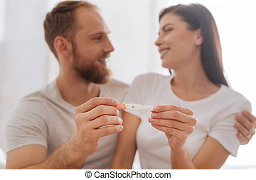 Young couple showing pregnancy test together