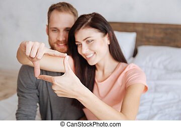 Millennial couple framing faces with hands - Say cheese....