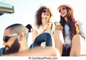 Party girls having fun in convertible car at the beach at sunset