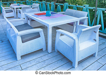 Al fresco cafe with white rattan wicker armchairs and tables...