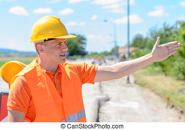 Young construction worker signalling with his hand showing a...