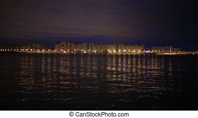 night city lights, municipal buildings shimmer on the water at night