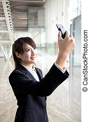Young businesswoman taking picture by camera in mobile phone