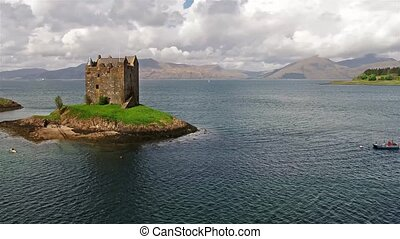 Canoes gathering around medieval Castle Stalker on the west...