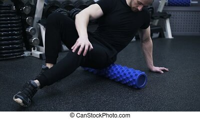 Close up of man working with his buttock on a roll in gym