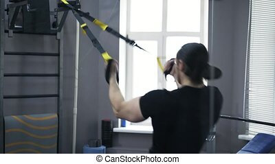 Rear view of man working out hands on gymnastic rings - Rear...