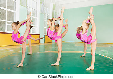Preteen girls practicing gymnastics in sports hall - Side...