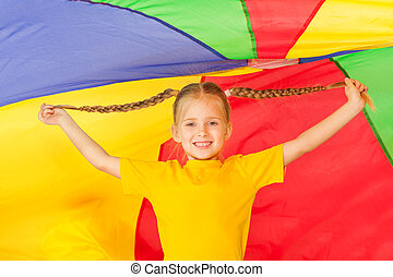 Cute little girl standing under colorful parachute