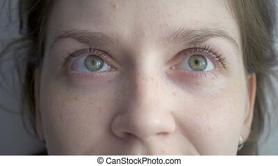 Caucasian blond woman rotating her green eyes, slow motion...