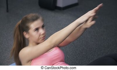 Close up of girl in pink doing situps in a gym