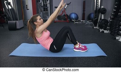 Woman in pink doing situps in a gym