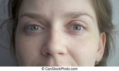 Blond woman squinting her green eyes, slow motion video