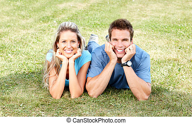 Love couple - Young smiling love couple on green grass