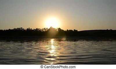Sunset over the river, boat sails along the river. Trees...