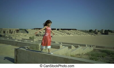 Little cute girl walks on the wall in big amphitheatre. Child have a dream. Kid jumps from fence. Pink dress flutters in the wind