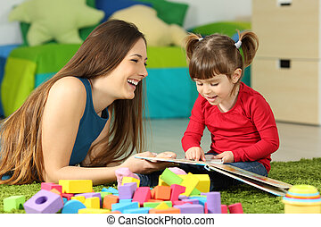 Mother and toddler playing with a book
