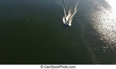Aerial shot of a modern motorboar turning back on the Dnipro river in the evening