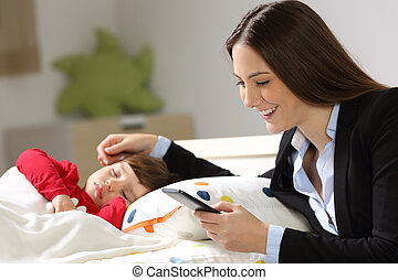 Worker mother working while her toddler sleeps - Worker...