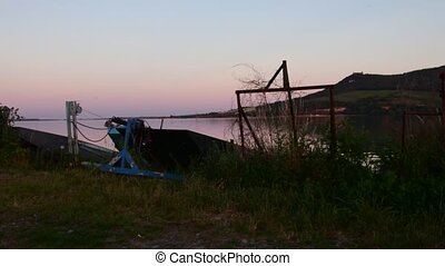 Summer lake. Panoramic view of old fishing boats. View of sunset.