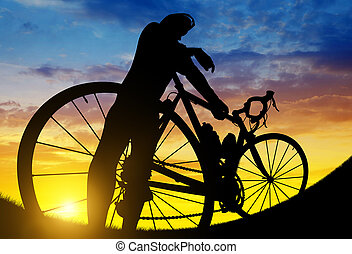 Cyclist on a road bike at sunset.