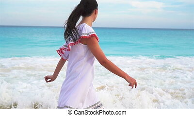 Young beautiful woman on white tropical beach. Girl walking...