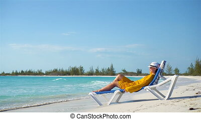 Young woman relaxing in sunbed on a tropical beach -...
