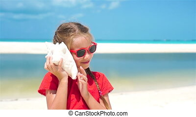 Portrait of little cute girl listening a big seashell on the beach. SLOW MOTION