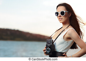 Retro Woman with Vintage Photo Camera on a Beach - Beautiful...