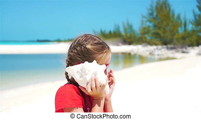 Portrait of little adorable girl listening a big seashell on...