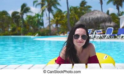 Happy girl having fun in swimming pool. Beautiful woman in...