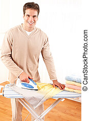 Housework - Happy young handsome man ironing clothes...