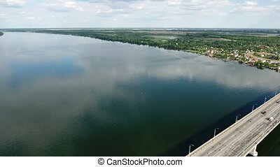 Aerial shot of the Dnipro river and modern automobile bridge...