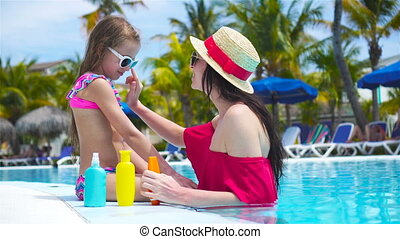 Young mother applying sun cream to kid hand outdoors - Young...