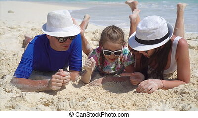 Young family on beach vacation - Young family of four on...