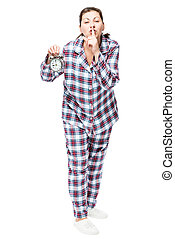 Young woman with an alarm clock in checkered pajamas showing...