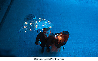 Guy and girl are looking at the camera on the night street