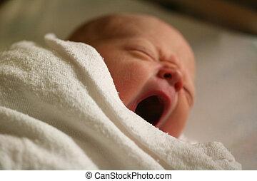 Newborn Baby Yawning - Newborn wrapped in blanket yawning