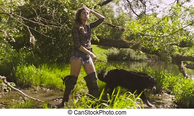 Young woman with a dog coming to the river - Woman in shorts...