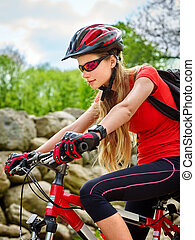 Woman on bicycle ride mountain. Girl traveling in summer park.
