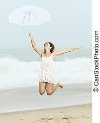 Monsoon - Beautiful woman near the stormy ocean at rain