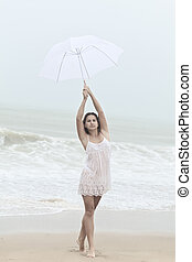 Monsoon - Beautiful woman near the stormy ocean at rain
