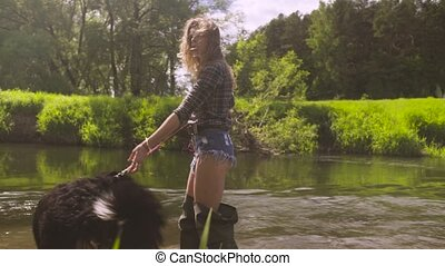 Young woman with a dog walking through the river - Woman in...