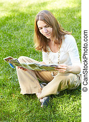 Woman - Beautiful woman reading a magazine in the summer...
