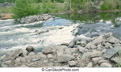 Water flowing through rocks. Boiling water in the river.