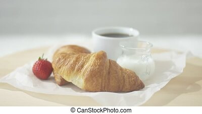 Croissants served with coffee - Close-up view of delicious...