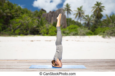 woman doing yoga in headstand pose on beach - fitness, sport...